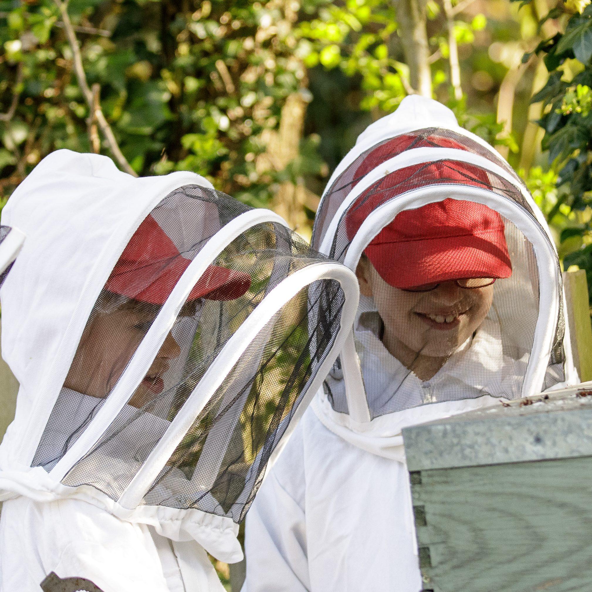 Children wearing bee keeping protective equipment